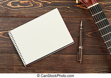Blank notebook, pen and guitar.