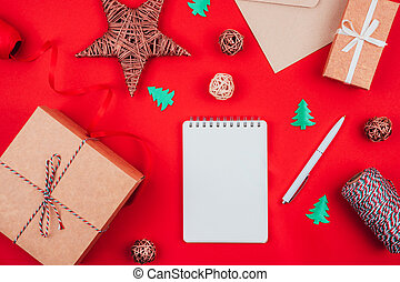 Blank notebook, pen, craft gift boxes, envelope, red bow, clew of tricolor rope, ribbon and decorations over red festive background. New year planning.