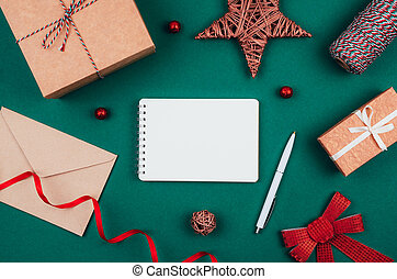 Blank notebook, pen, craft gift boxes, envelope, red bow, ribbon and decorations over green festive background. New year planning.