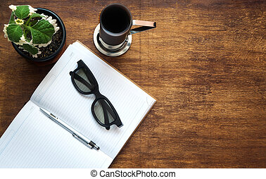 Blank notebook with black glasses, pen and cup of coffee are on top of wood table. Flat lay