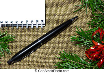 Blank notebook with black pen, fir branches on top of a burlap