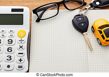 Car key on blank notebook with calculator on wood table