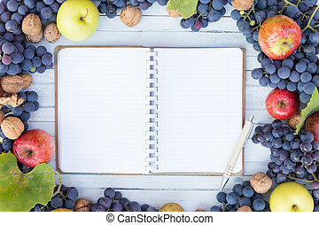 Blank notebook with copyspace and autumn fruits frame