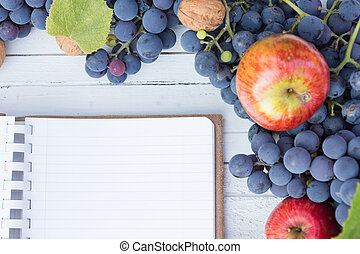 Blank notebook with copyspace and autumn grapes