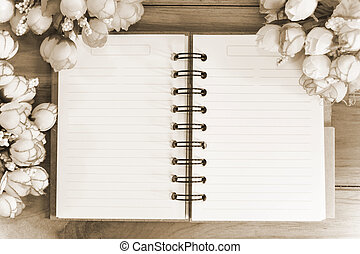 Blank notebook with flower on wooden background