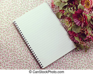 blank notebook with flower on wooden table