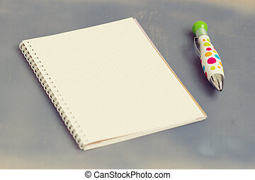 blank notebook with pen and pencil on wooden table