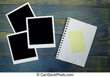 blank notebook with sticker and photo frame on wooden background