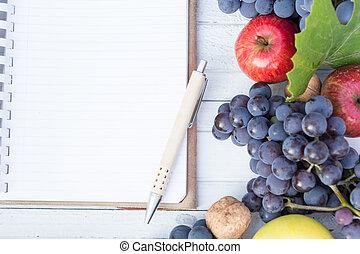 Blank notebook with wooden pen and autumn grapes