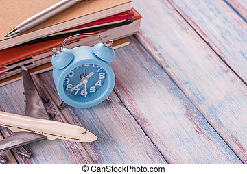 Blank notebook,airplane toy,pen and alarm clock on office desk with wooden background.
