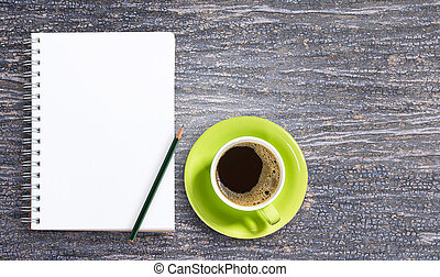 Blank notepad and pencil with cup of coffee on wooden