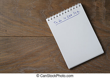 blank notepad on wooden table with phrase to do in 2017
