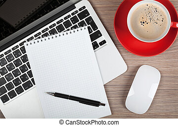 Blank notepad over laptop and coffee cup on office wooden...