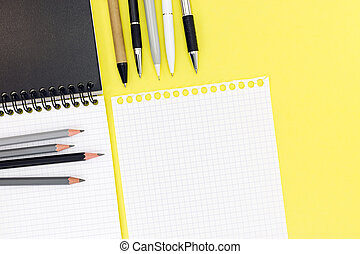 blank notepad, piece of white paper, ballpoint pens and pencils on yellow background