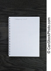 blank notepad with chequered pages on gray wood table with shopping list phrase