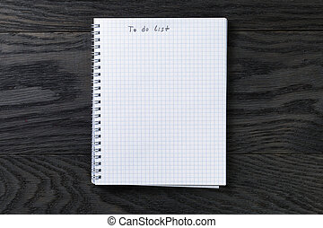 blank notepad with chequered pages on gray wood table with to do list phrase