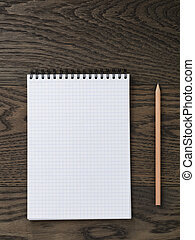 Blank notepad with pen and pencil on office wooden table
