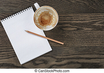 Blank notepad with pencil and empty coffee cup on wooden table