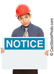 A man wearing a hardhat and holding a blank notice or safety sign