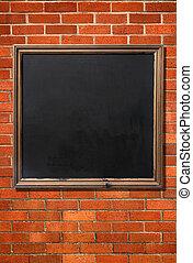 Blank old menu blackboard on a brick wall ready for text.