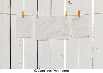 Blank old paper hanging on white wood background with space for text.