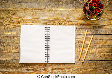Blank opened notebook with flower on wooden table