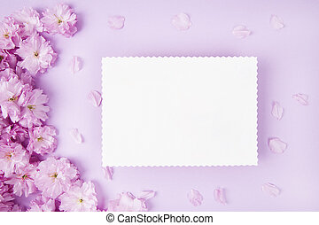 Blank paper and cute pink flowers on pink background