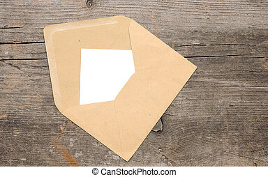 Blank paper and envelope on old wooden background