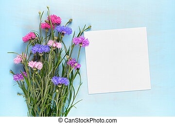 Blank paper card and cornflowers on blue wooden background