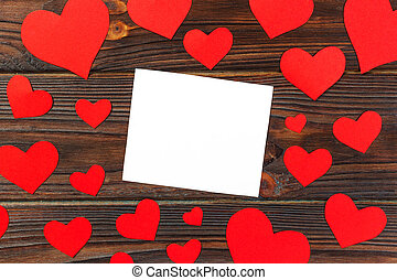 blank paper note with red heart shape on grunge wooden background