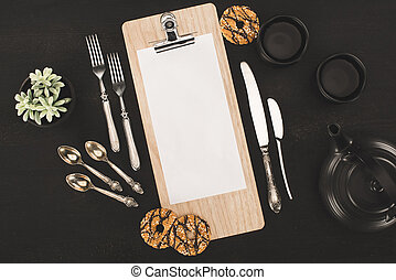 blank paper on clipboard and cookies