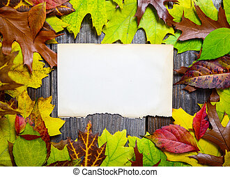 Blank paper on wooden table with autumn leaves