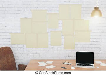 Blank paper posters on white brick wall with laptop in loft room, mock up