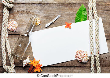 Blank paper sheet on weathered wood background with rope, shells, leaf and flowers