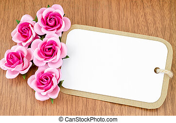 Blank paper tag and pink roses