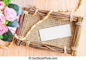 Blank paper tag in sack photo frame with beautiful flower