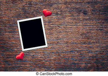 Blank photo frame and red heart on wood background with...
