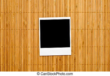 Blank photo frame on bamboo
