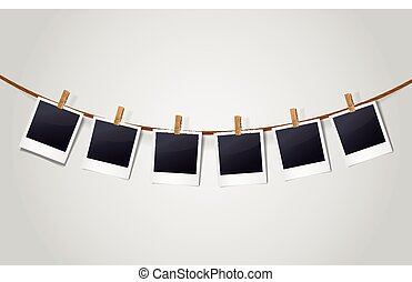 blank photo frames on a clothesline isolated on white