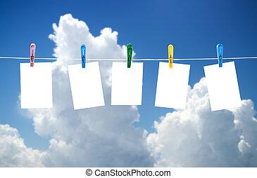Blank photos hanging on a clothesline, blue sky on...