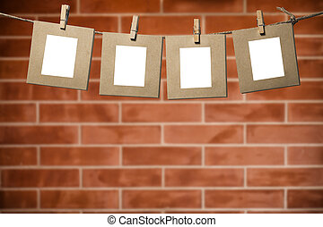 Blank photos hanging on a clothesline over brick wall background with copy space