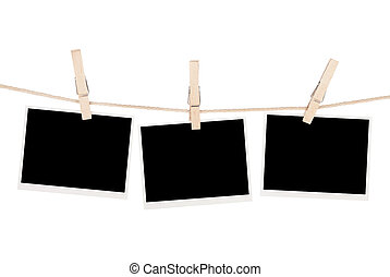 Blank photos hanging on clothesline. Isolated on white...