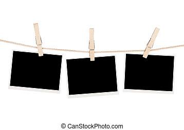 Blank photos hanging on clothesline. Isolated on white background