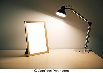 Blank picture frame with lamp on wooden table, mock up
