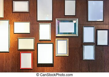 Blank picture frames on a wall gallery
