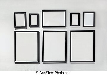 Blank picture frames on white wall