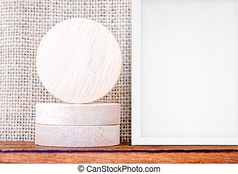 Blank piece of round wood and white photo frame on wood...
