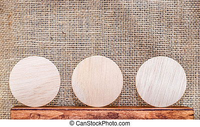 Blank piece of round wood on wood table and sack fabric...