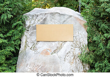 Blank plaque on the stone. Bronze memorial plaque in the park. Empty sign board on the wall