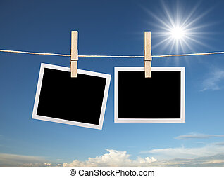 blank polaroid hanging on clothesline with sunny day
